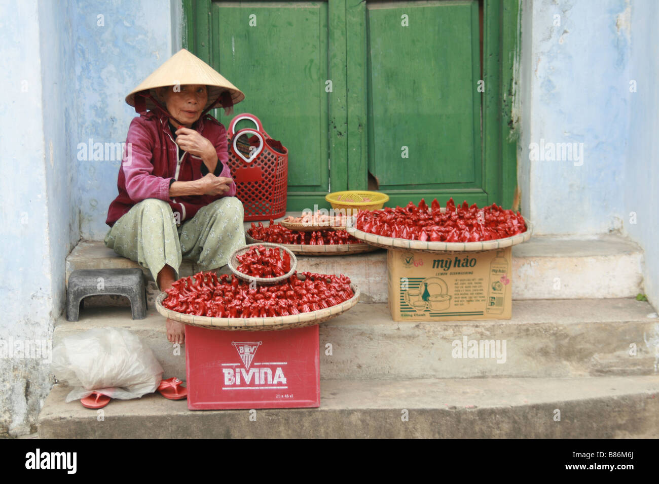 Photograph of a Vietnamese lady selling red whistles on the street in Hoi Ann, Vietnam - Stock Image