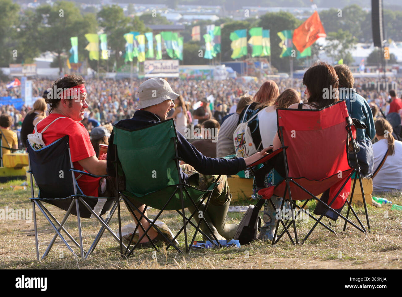 A group of friends enjoy the sunshine in front of the crowds at the Glastonbury Festival in Pilton, Somerset in - Stock Image