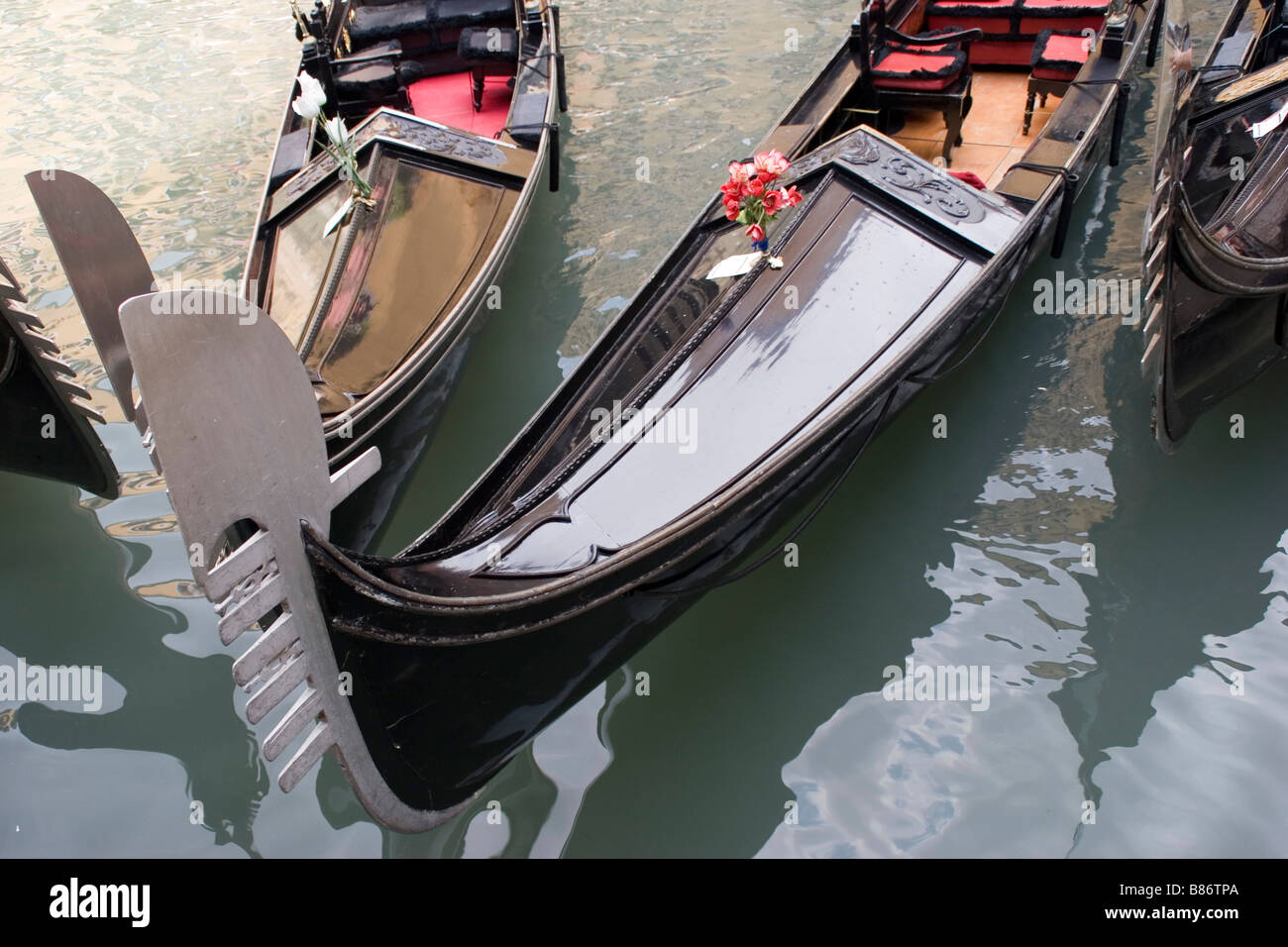 Venice Italy gondolas wait for passengers before gondoliers embark on tours of the city's famous canals. - Stock Image