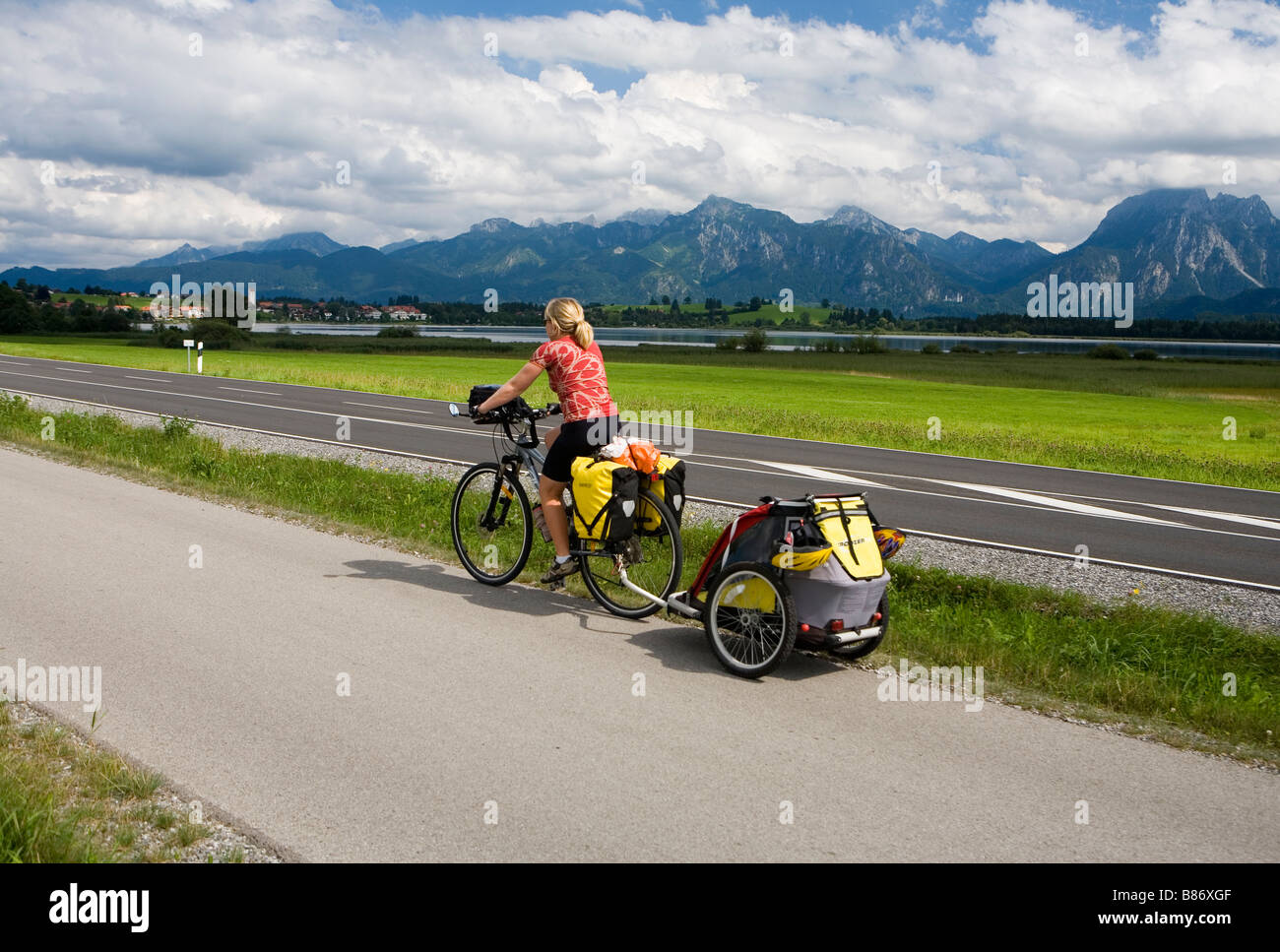 Cyclist towing a child trailer near Hopfensee on the Bodensee-Koningsee Radweg - Stock Image