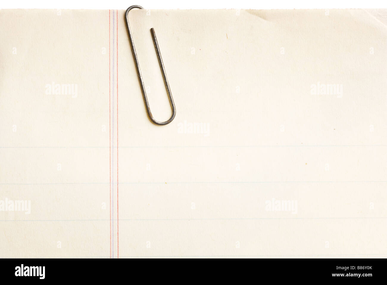 old lined paper with rusty paperclip attached - Stock Image