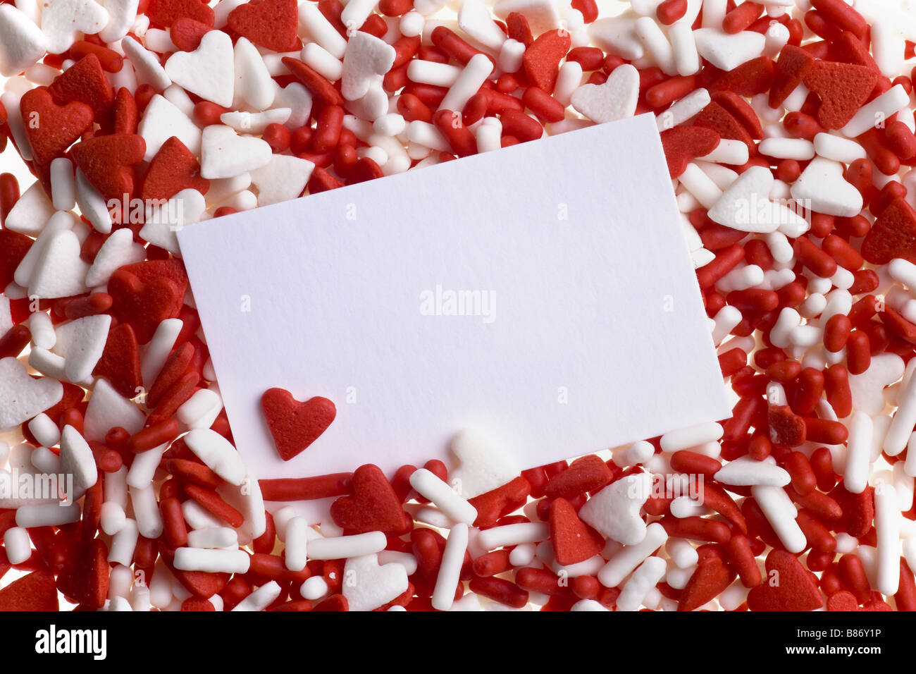 Valentine red and white heart sprinkles background with card - Stock Image