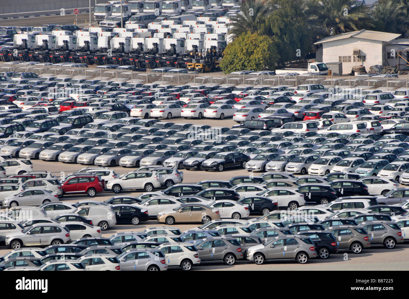 Abu Dhabi looking down on dockside storage of imported new cars and trucks awaiting distribution - Stock Image