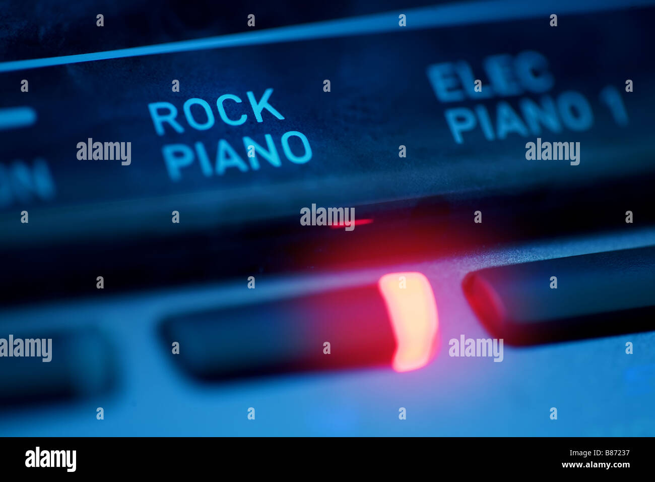 closeup of a digital piano with the 'rock piano' sound style button turned on - Stock Image