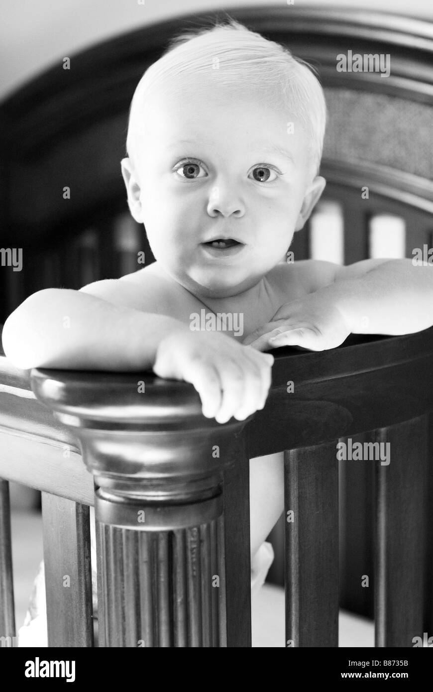 Baby standing in crib - Stock Image