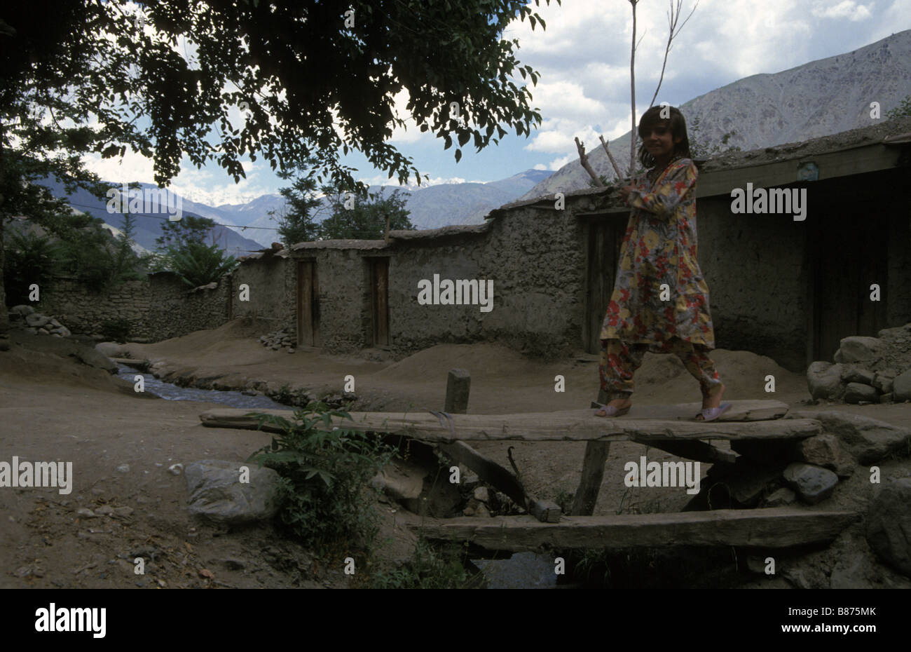 Pakistani girl on wooden bridge in back street Chitral Pakistan - Stock Image
