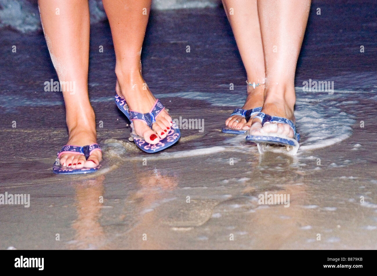 d3f9f7d2b5d4 Two pairs of feet walk in shallow water wearing flip flops Model released