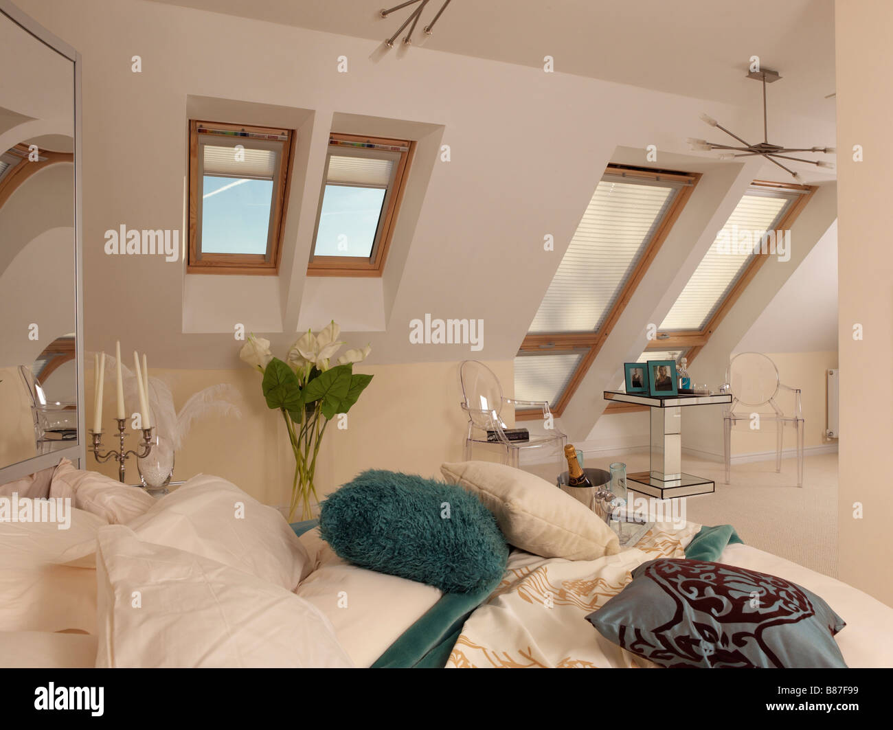 blue and cream bedroom with velux windows and small table ...