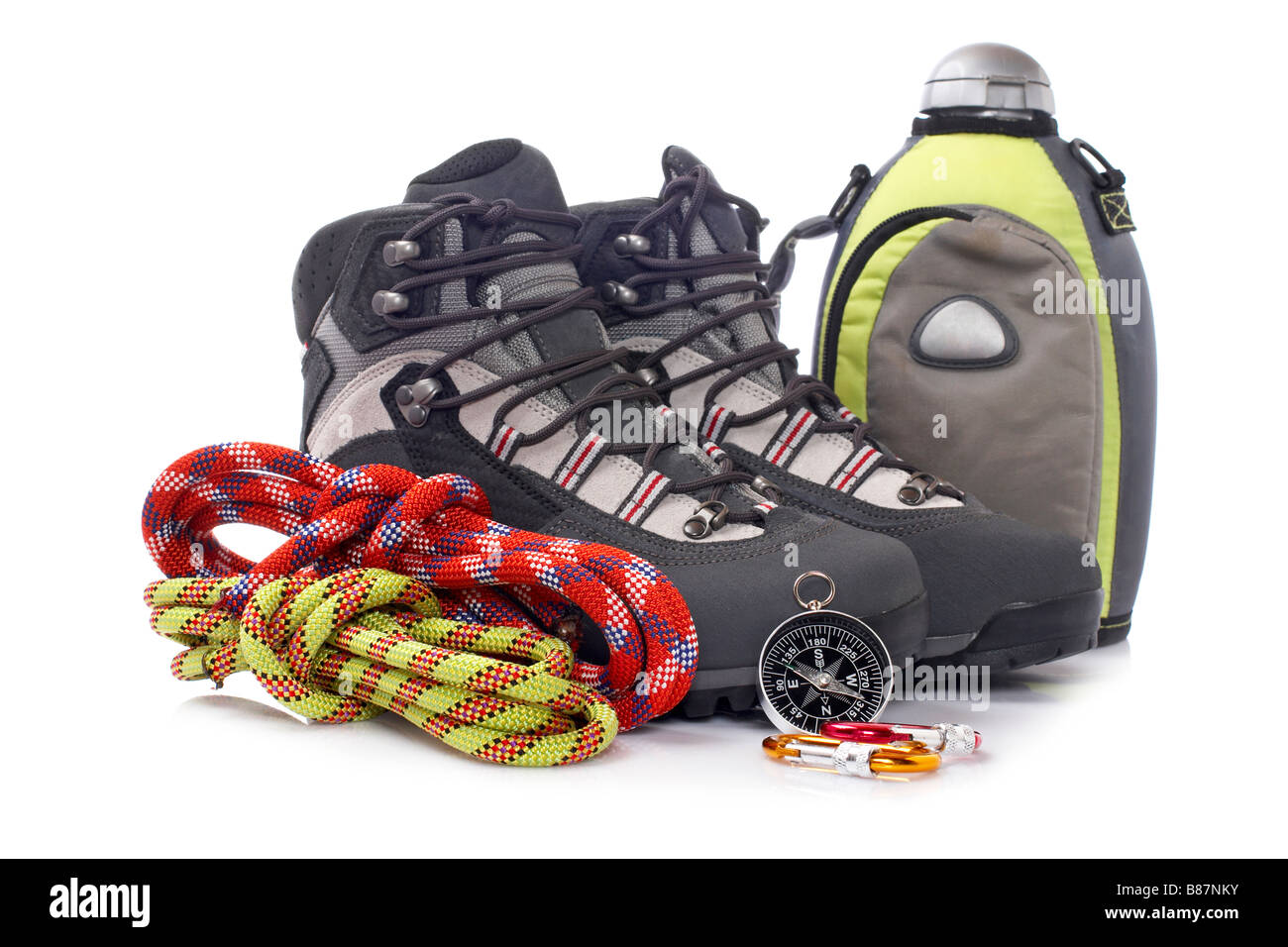 Hiking boots, canteen, two rope and compass reflected on white background - Stock Image