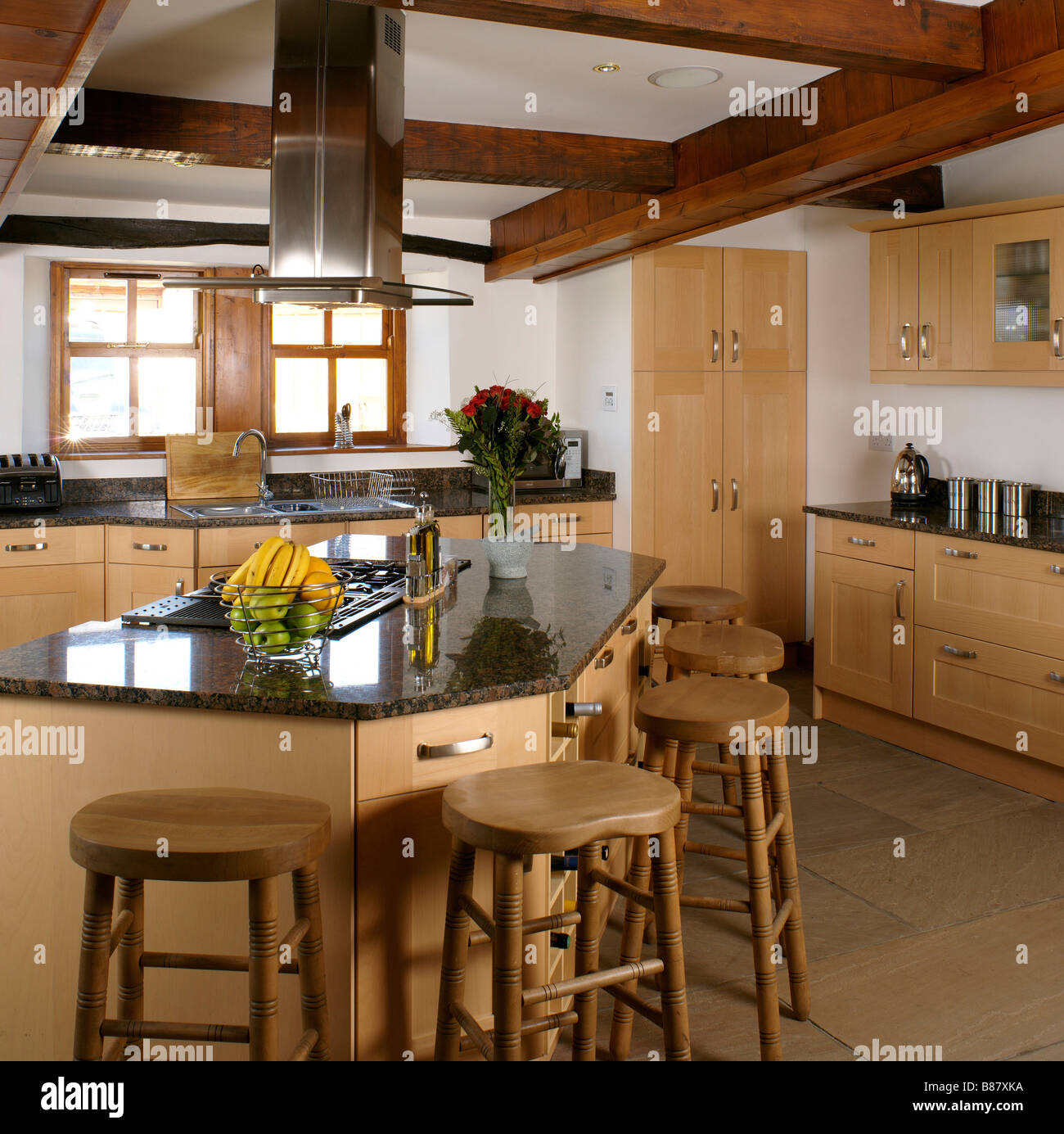 large wooden kitchen with central island unit and breakfast bar ...