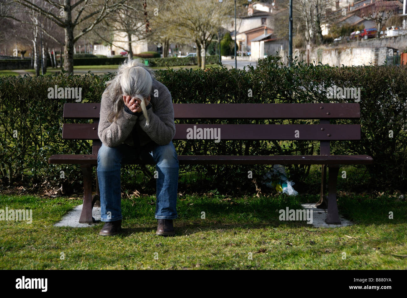 Stock Photo Of A Woman Sitting Alone On A Park Bench With Her Head