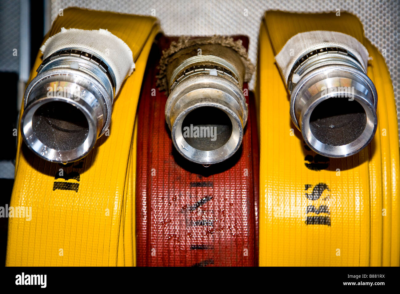 Yellow and red fire hoses - Stock Image