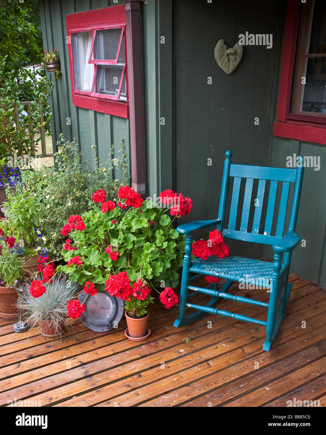 Vashon Island, WA: Colorful deck with potted flowers and blue rocker in the village of Ellisport - Stock Image