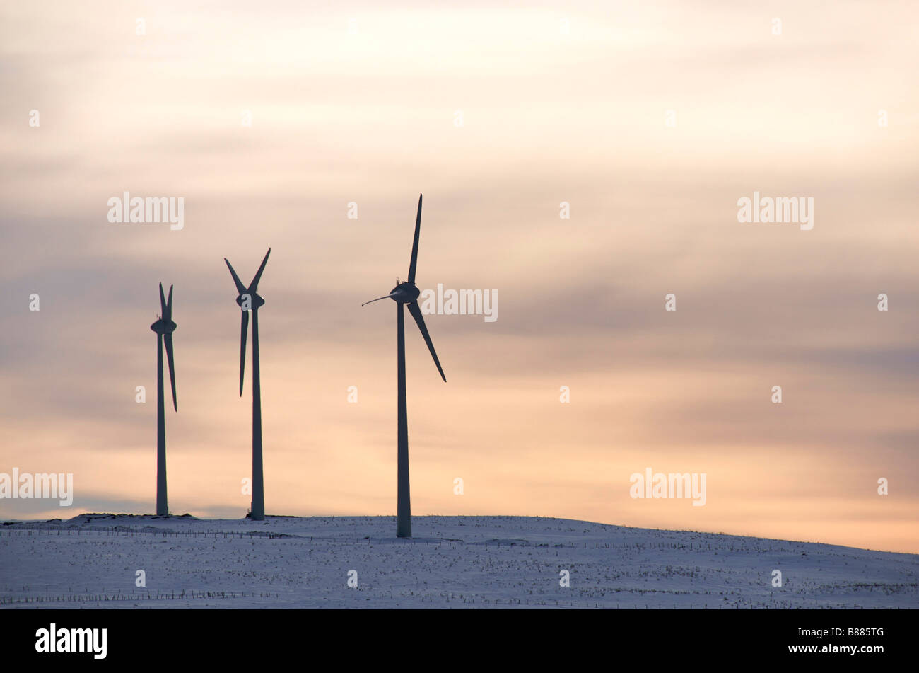 Wind turbines on a hill at sunset - renewable energy - Stock Image