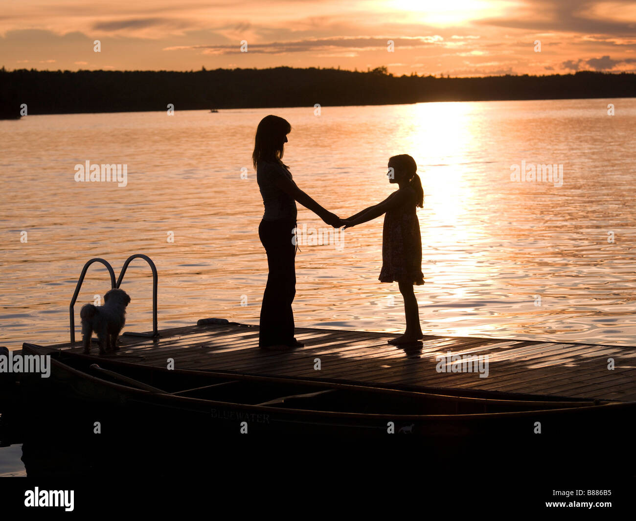 Silhouette of mother and daughter on a dock, Lake of the Woods, Ontario, Canada - Stock Image