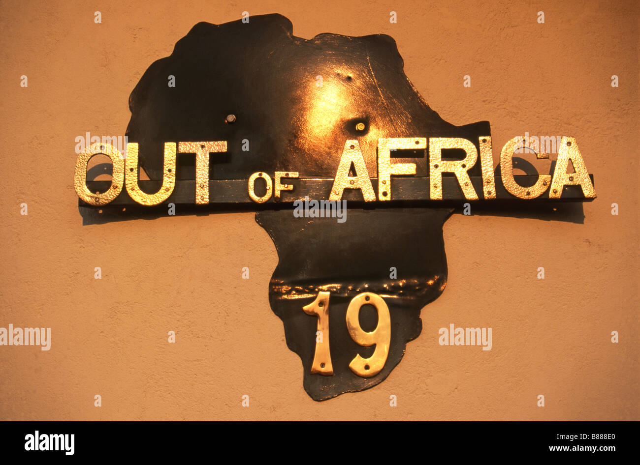 Sign with map of Africa and words 'OUT OF AFRICA' in gold lettering superimposed - Stock Image