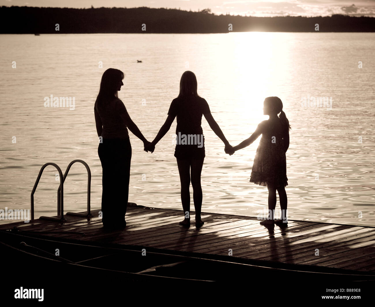 Lake of the Woods, Ontario, Canada; Silhouette of three females on a dock - Stock Image