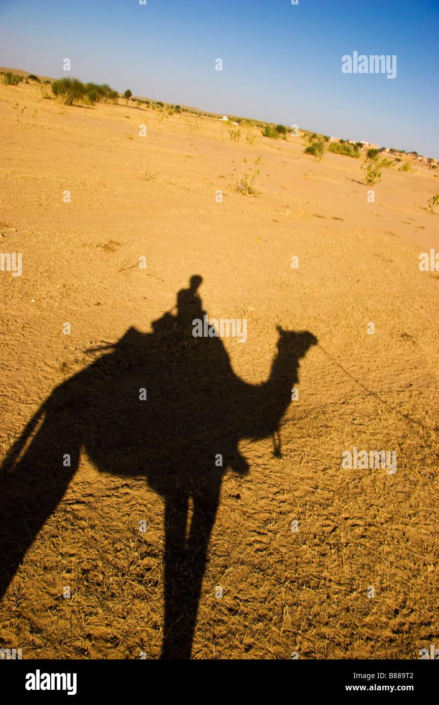 Tourist rides camel in desert Khuri Rajasthan India - Stock Image