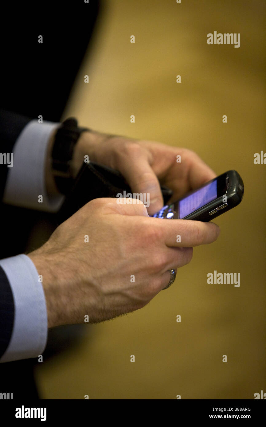 businessman text messaging from his Blackberry phone - Stock Image