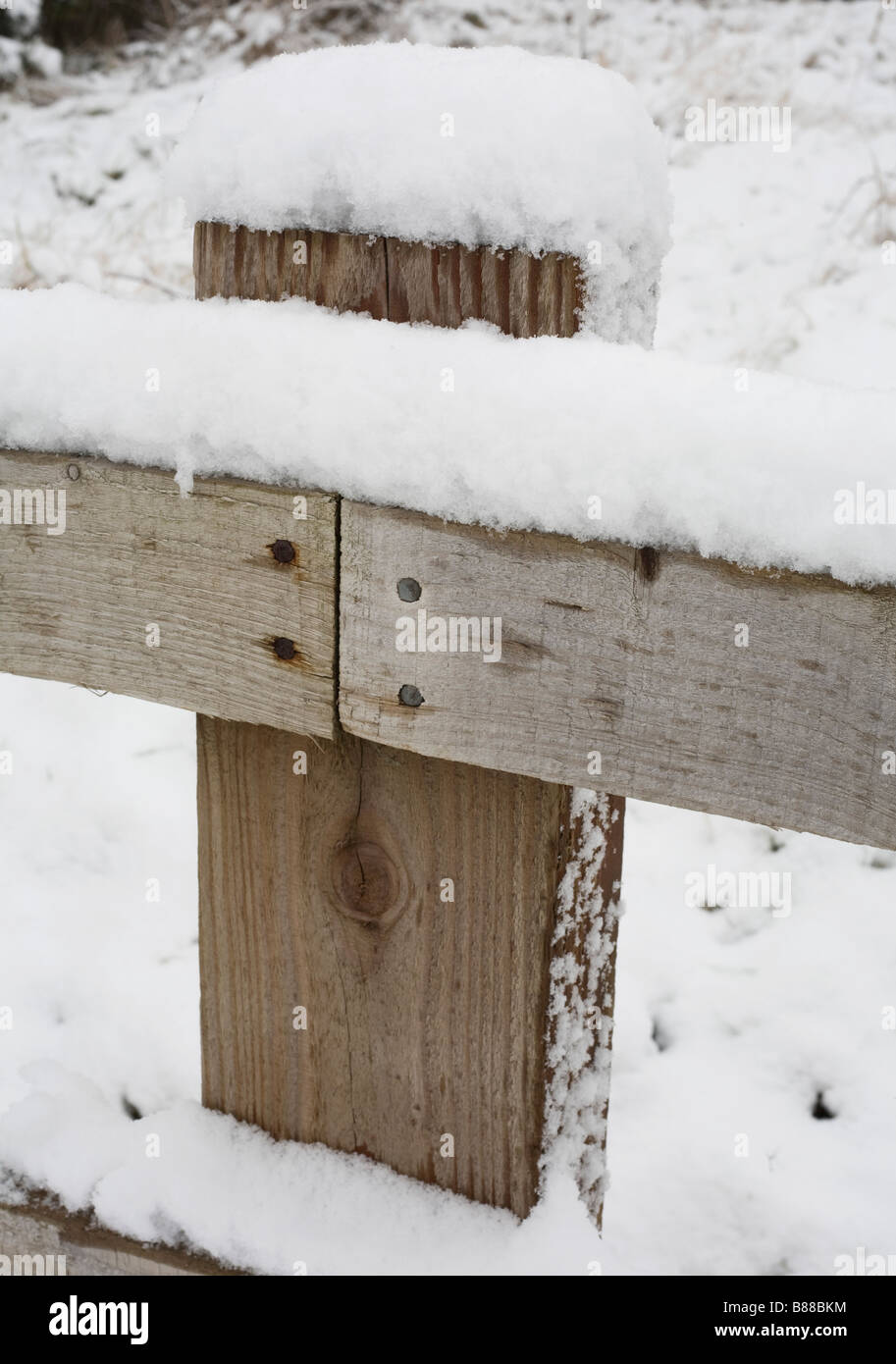 a wooden fencepost with snow settled on it after rare snowfall on the coast of South Wales - Stock Image