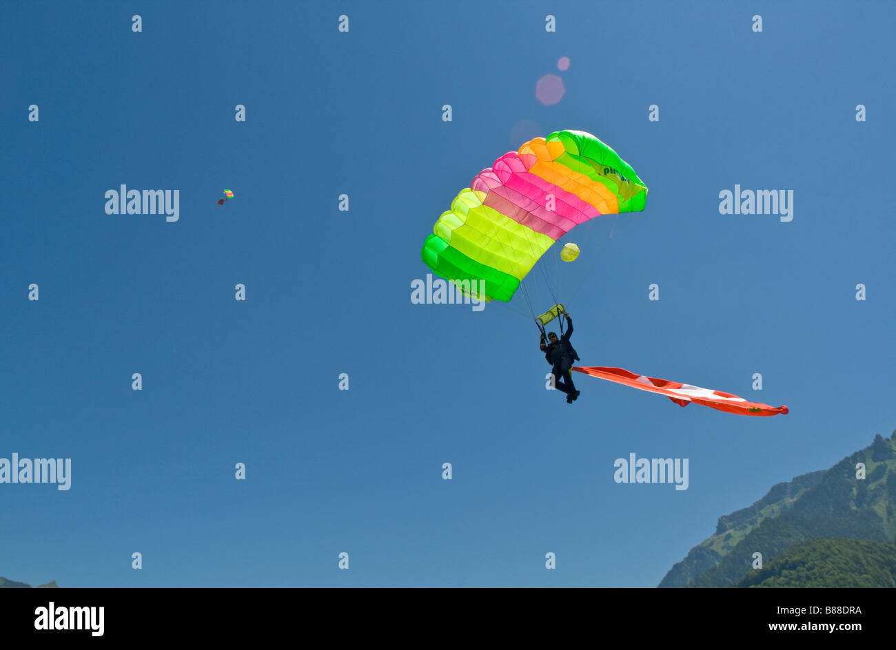 Skydiver under canopy is going to land with a big Swiss flag behind him.With this demo jump the diver is representing - Stock Image