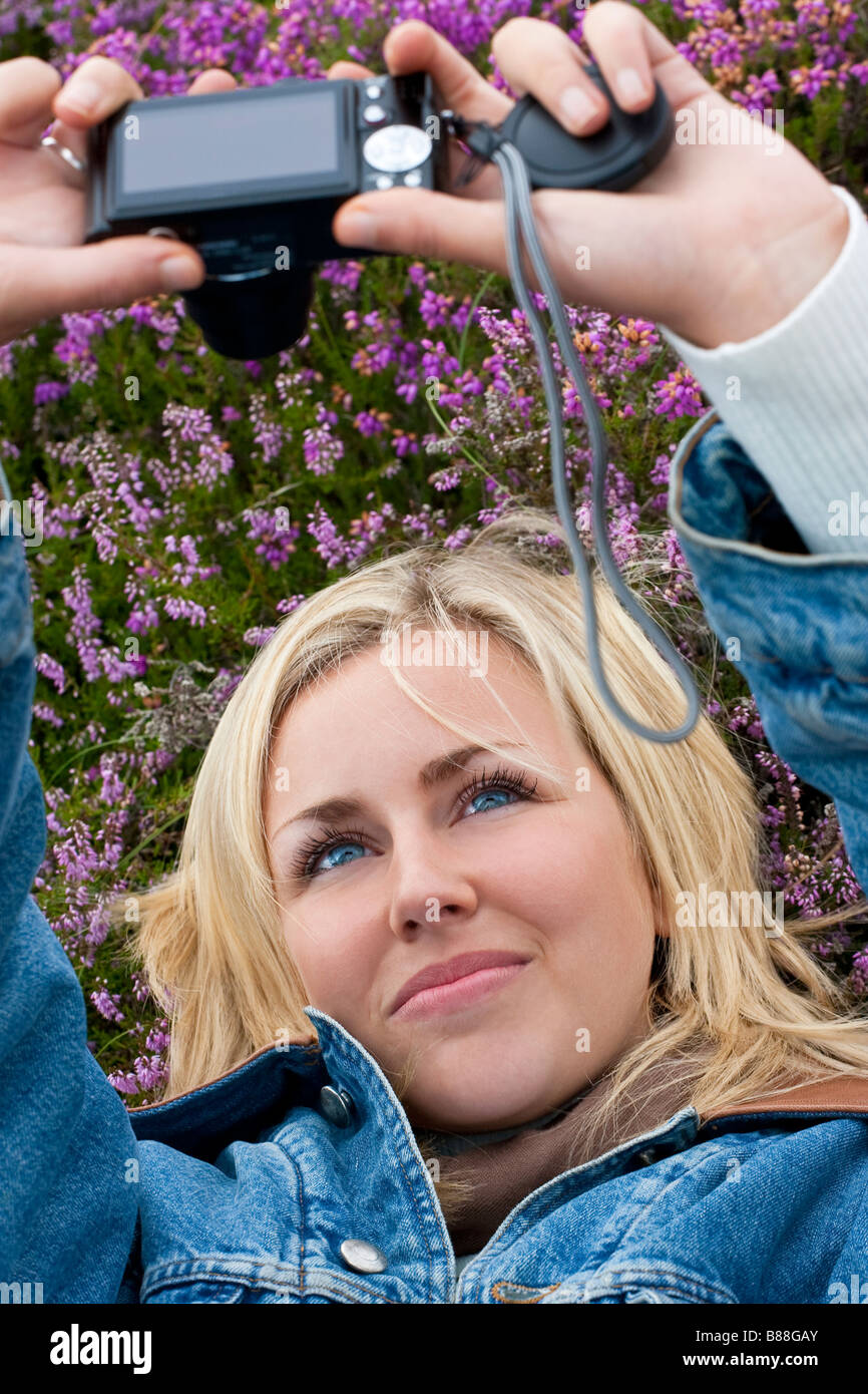 A beautiful blond haired blue eyed young woman laying down in a field of heather and taking a self portrait on her - Stock Image