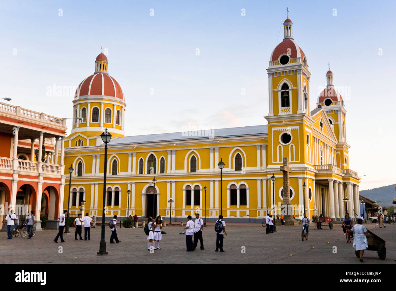 School children playing in the Parque Central in front of Our Lady of the Assumption Cathedral or Granada Cathedral - Stock Image