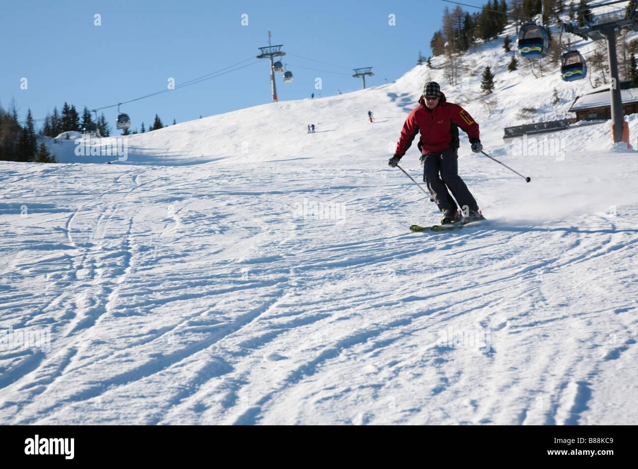 Rauris Austria Downhill skier skiing down Rauriser Hochalmbahnen ski slope piste in Austrian Alps in winter snow - Stock Image