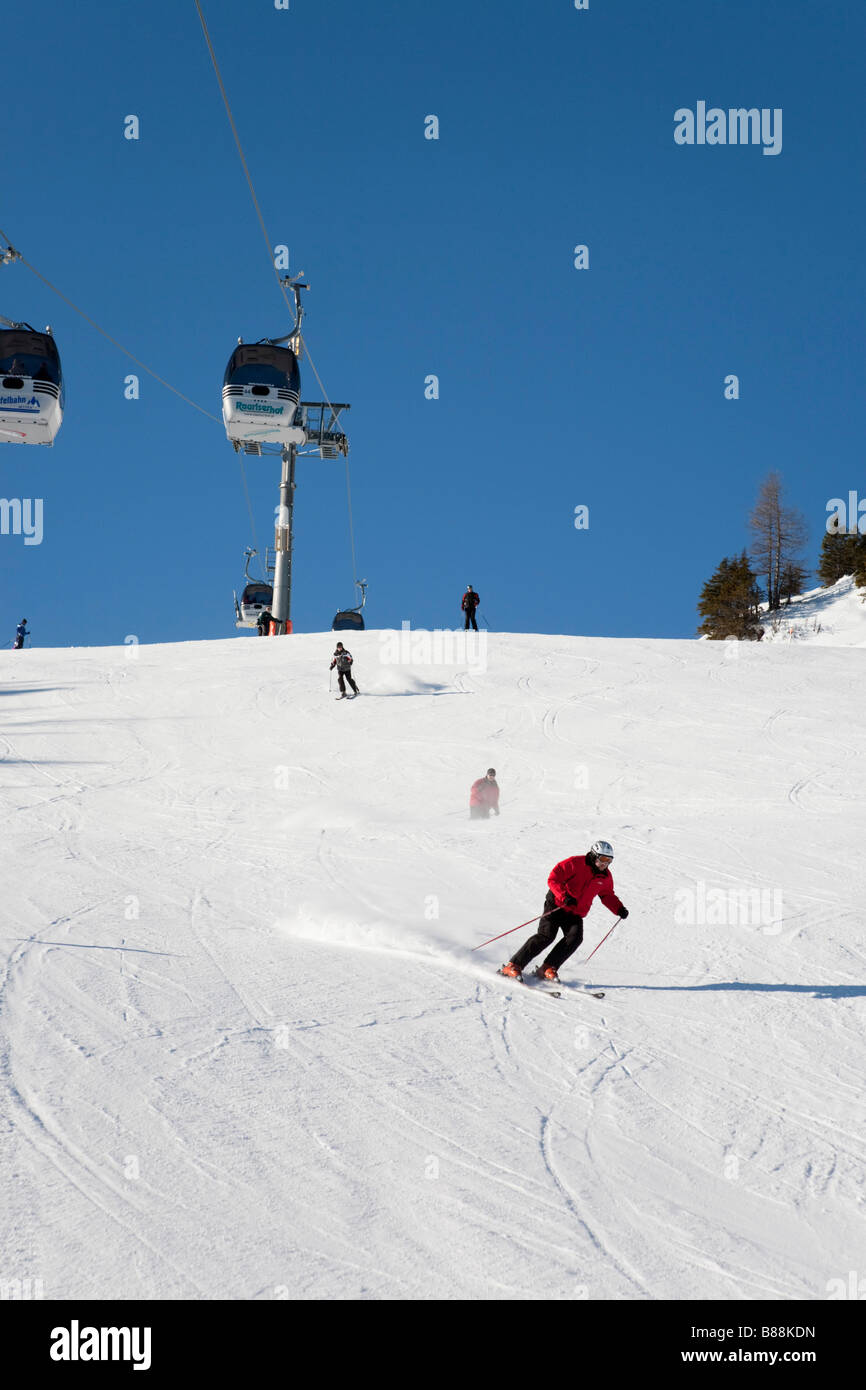 Rauris Austria  Downhill skier skiing down Rauriser Hochalmbahnen ski slope piste in Austrian Alps in winter - Stock Image