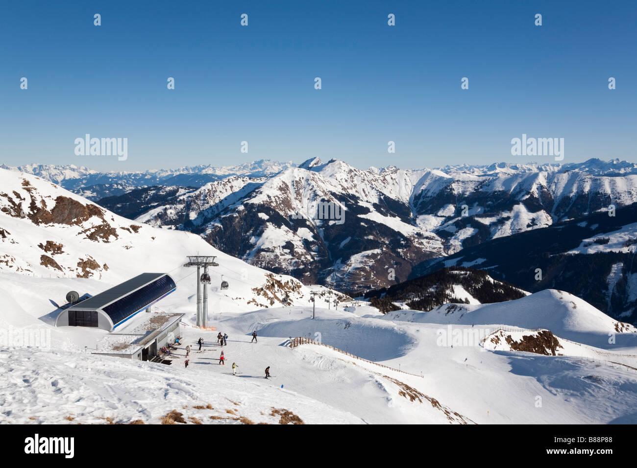 View above Rauriser Hochalmbahnen ski slopes with skiers skiing in alpine resort in Austrian Alps in winter. Rauris - Stock Image