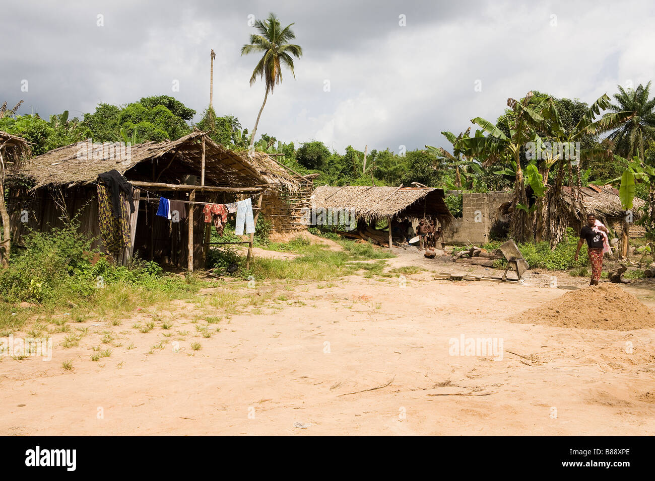 Scenic view of a remote Nigerian village in the middle of the jungle. Clothes are drying on a line but a storm is - Stock Image