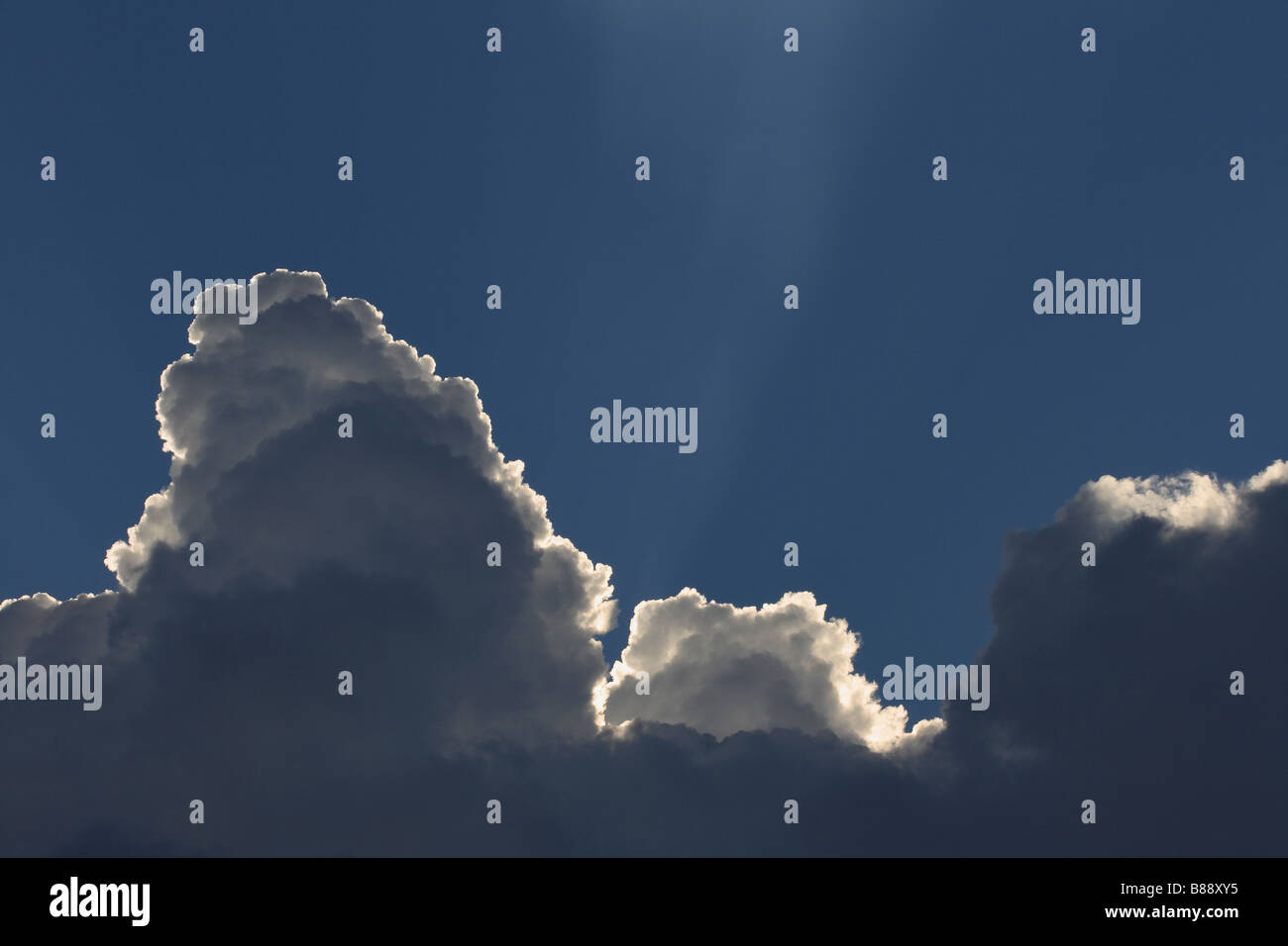 cumulonimbus cloud or storm clouds with light beams or streams above - Stock Image