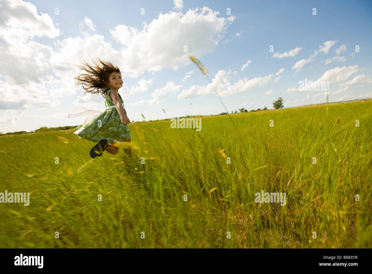 Girl Running Through A Grassy Field In North Dakota Stock