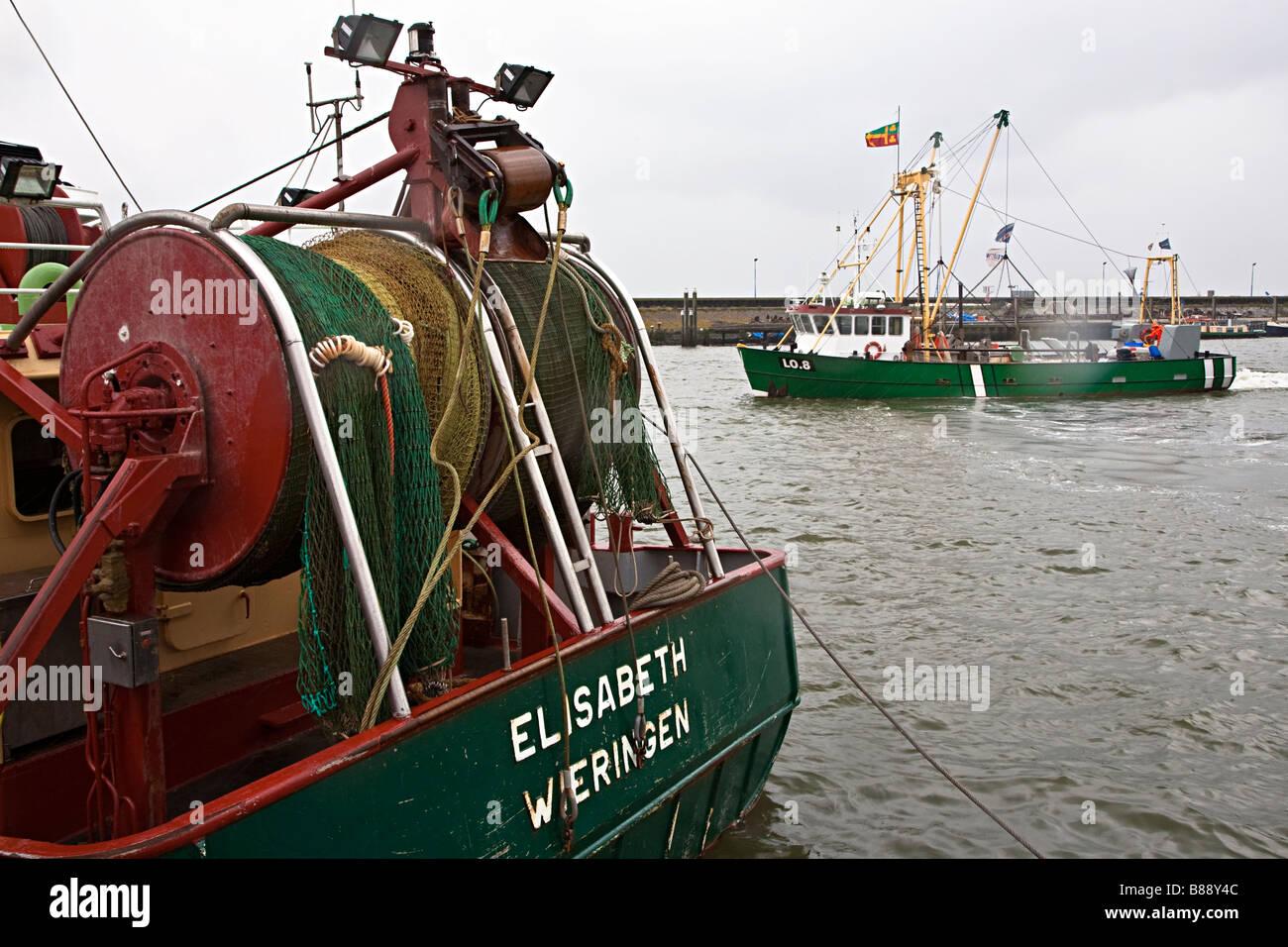Fishing boats leaving harbour Den Oever Wieringen Netherlands - Stock Image