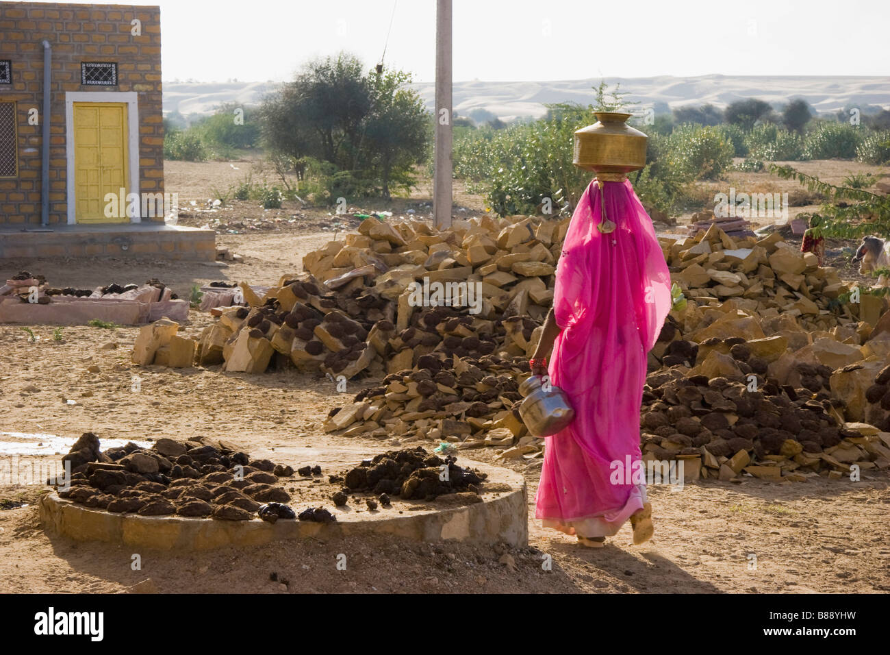 Indian woman carries water pot on head Khuri desert Rajasthan India - Stock Image