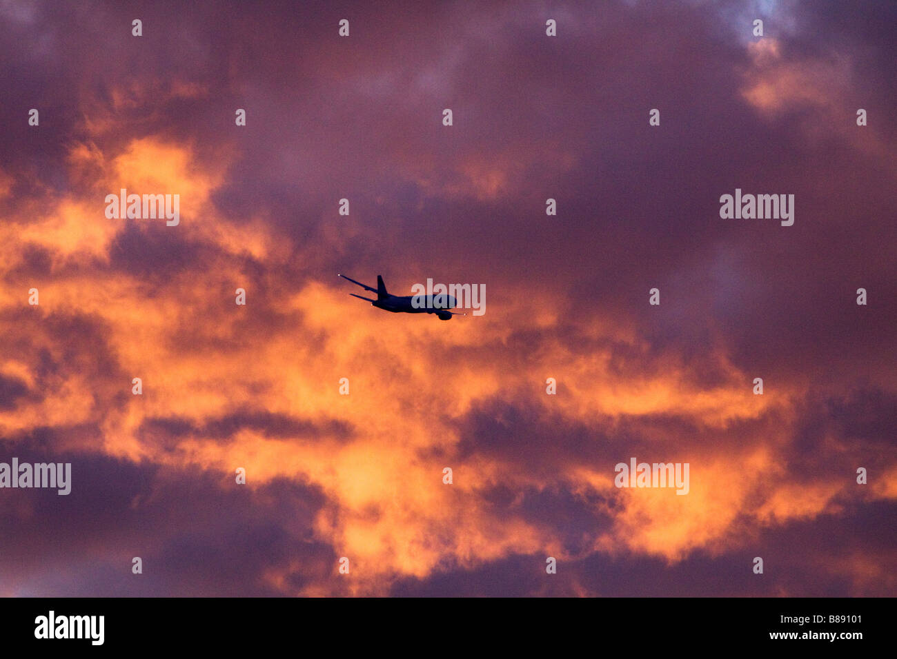 Commercial jet Plane at sunset heading toward dramatic fiery clouds - Stock Image