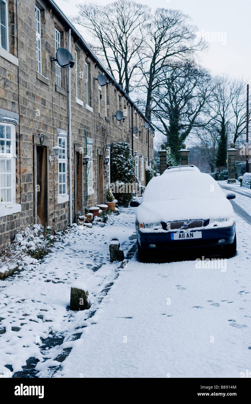 A car parked by its house on a snow covered street. Stock Photo