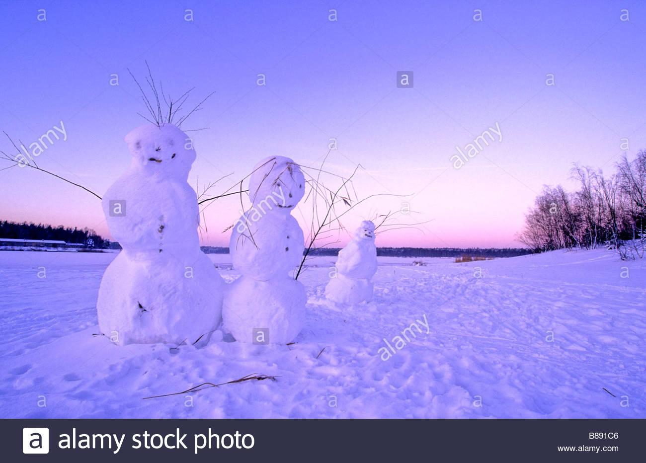 snowman family next to lake Germany Schneemannfamilie neben einem See - Stock Image