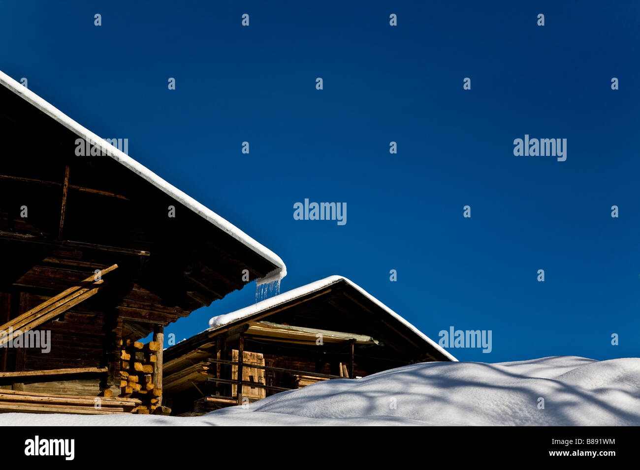 Snow covered wooden chalets with vivid blue sky Les Saises French Alpes - Stock Image
