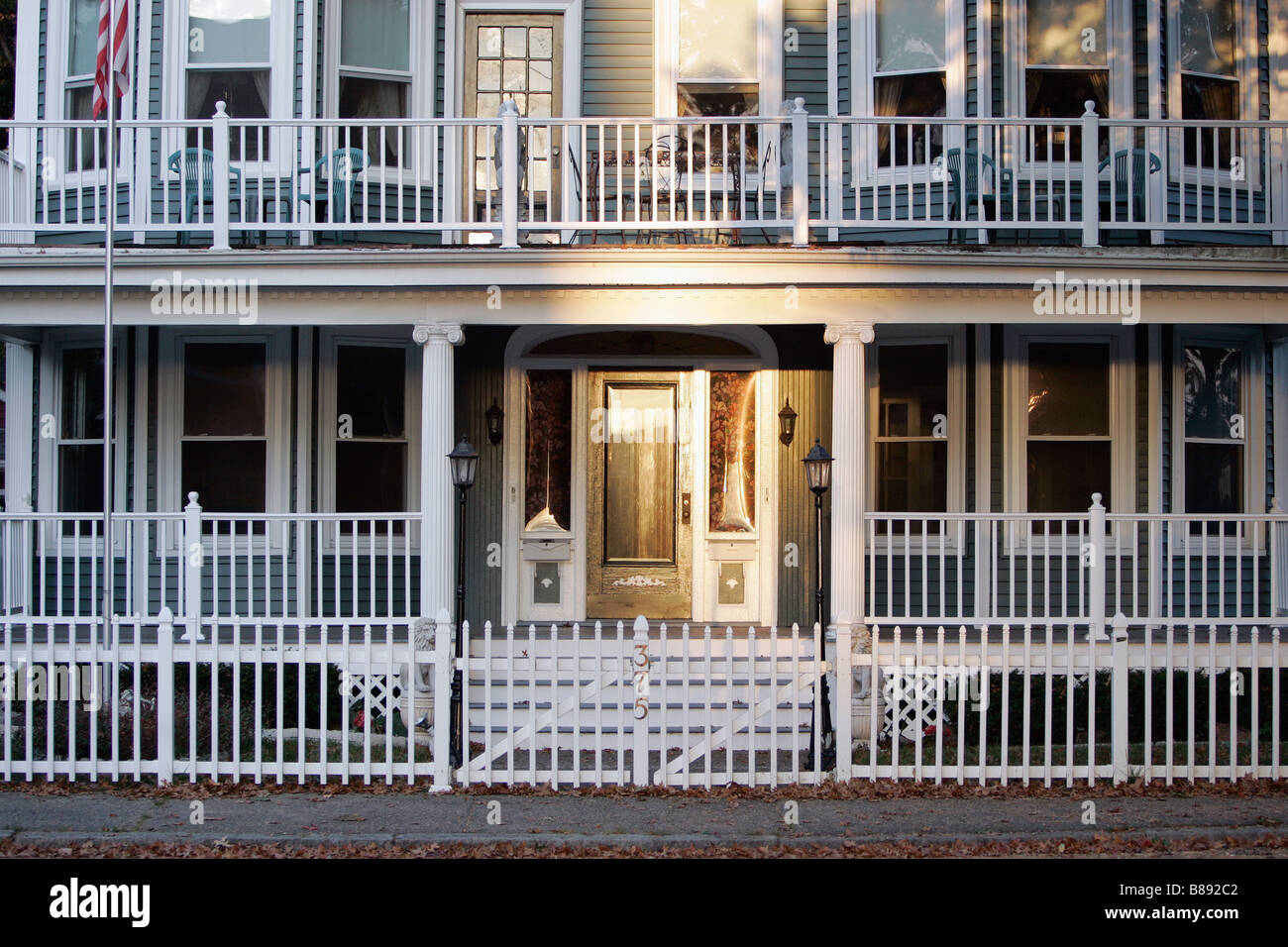 House white fence porches two story balcony - Stock Image