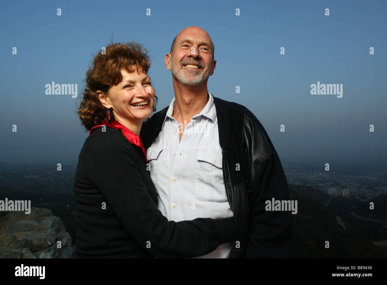 Happy mature couple embracing outdoors ontop of a city Stock Photo