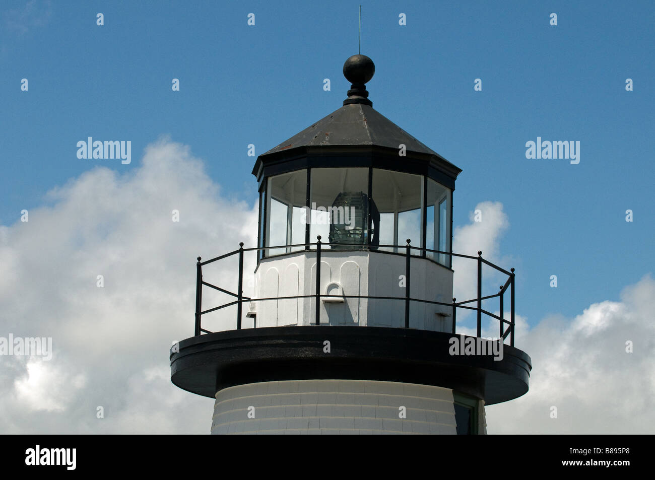 Light house against backdrop of blue skies and fluffy white clouds - Stock Image