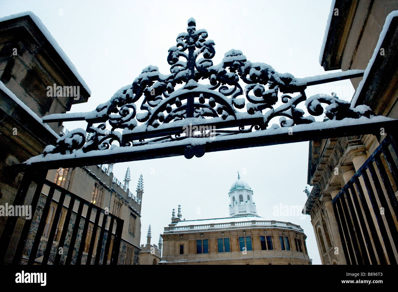 The gate leads to Sheldonian Theatre a Wren Building with Clarendon Building on the right in the snow Stock Photo