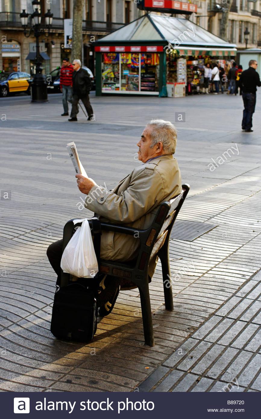 Reading the morning newspaper in La Rambla, Barcelona Spain - Stock Image