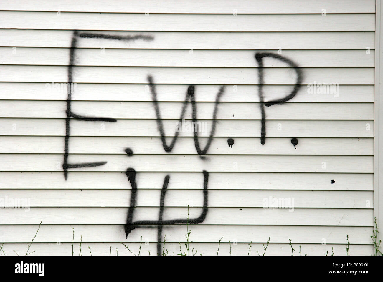 Gang markings of the East Warren Posse sprayed on the side of a house in Detroit Michigan USA - Stock Image