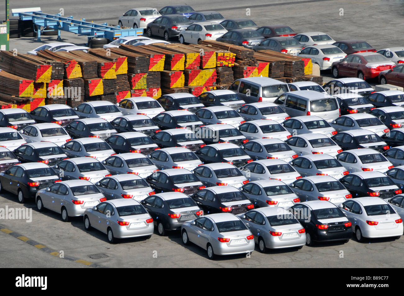 Bahrain looking down close up on dockside storage of imported new cars and large piles of timber awaiting distribution - Stock Image