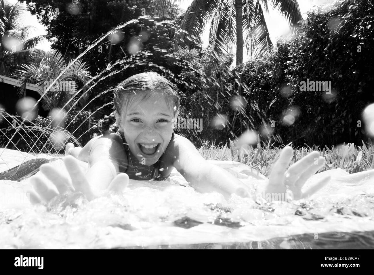 child playing on water slide on grass - Stock Image