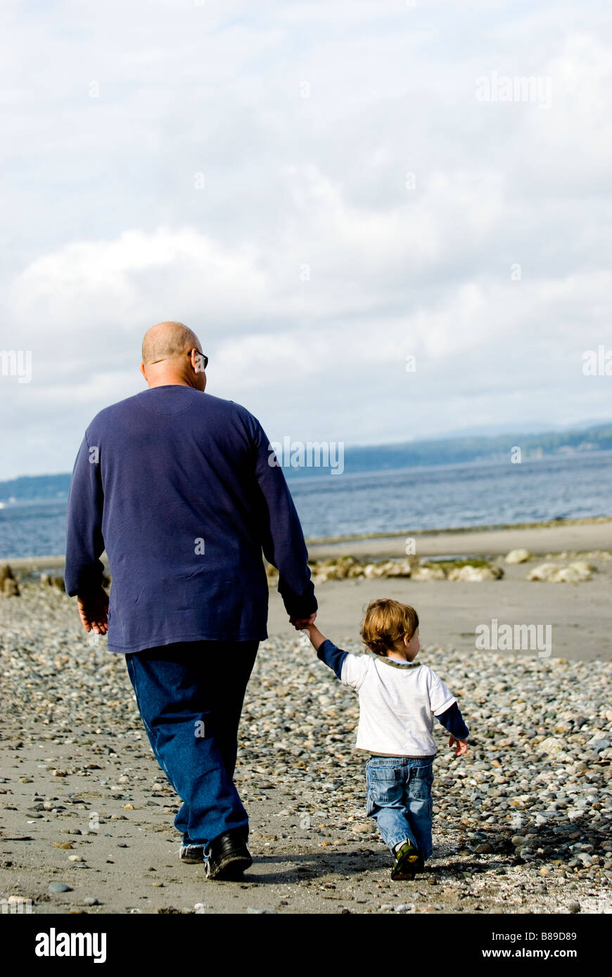 Father holds hands with his son on the beach. - Stock Image