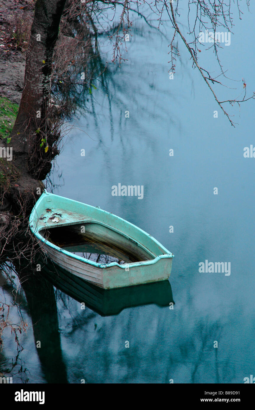 Sink boat floating river bank melancholy reflex water light blue environment loneliness abandonment broken fall - Stock Image