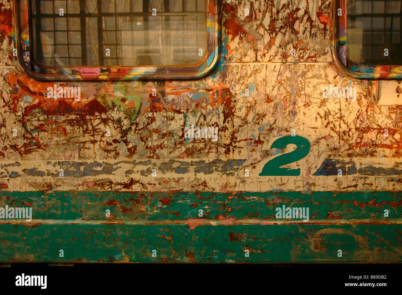 Graffiti vandalism scratches second class 2 carriage car Italian railways Milano Milan stazione centrale rust FFSS - Stock Image